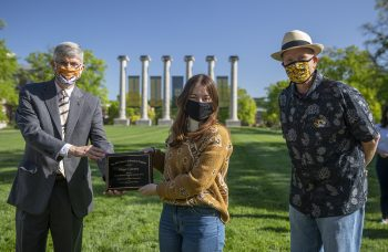 Jim Spain presents Hesburgh scholarship plaque to Maggie Courtney while William Horner stands by.