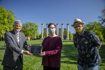 Jim Spain presents Hesburgh scholarship plaque to Brandon Ford while William Horner stands by.