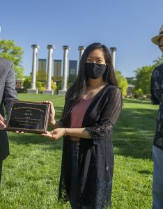Jim Spain presents Hesburgh scholarship plaque to Alice Yu while William Horner stands by.
